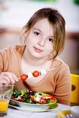 Young girl eating salad at home. A studio shoot — Stock Photo