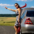 Woman hitch-hiking - Stock Photo