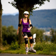 Young woman on rollerblades in the country — Stock Photo #6101607