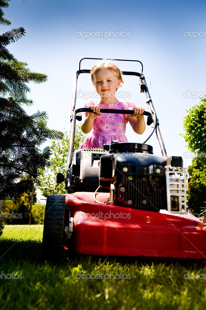 A 3,5 years old girl working in the garden with lawnmower — Stock Photo #6100342