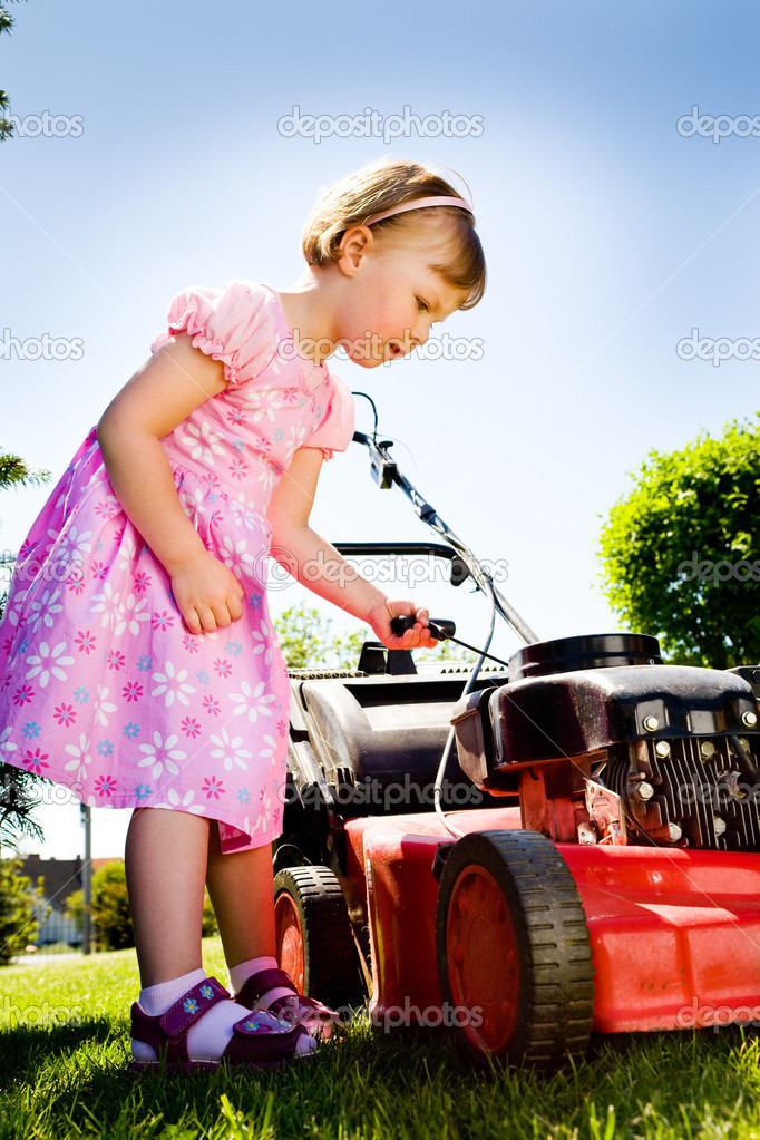 A 3,5 years old girl with lawnmower in the garden — Stock Photo #6100353