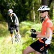 Stock Photo: Two women cycling in the forest