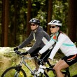 Two women cycling in the forest — Stock Photo