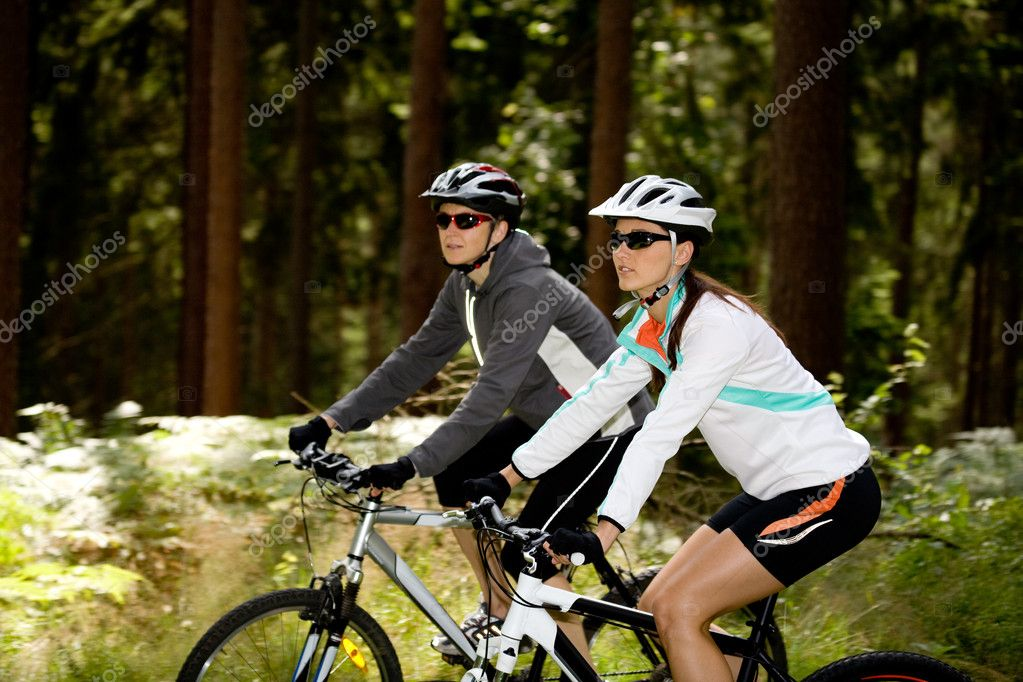 Two women riding bikes through the forest — Stock Photo #6170460