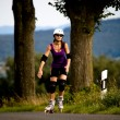 Young woman on rollerblades in the country — 图库照片