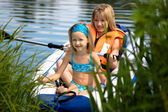 Two young girls boating on the lake — Stock Photo