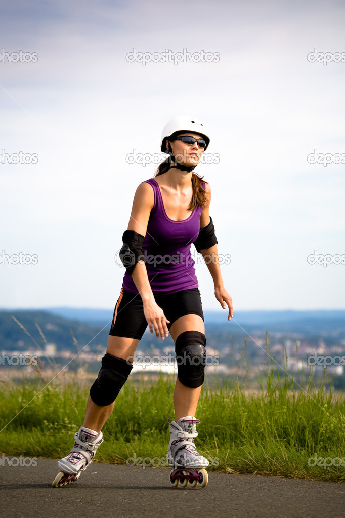 A portrait of a young woman running on the roller skates in the country  Stock Photo #6219469