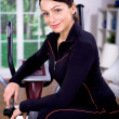 Gym girl on cross-trainer — Stock Photo