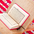 Warsh quran open on a wooden stand on a red Moroccan rug — Stock Photo #6172611