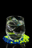 Glass with ice and water on gravel — Stock Photo
