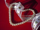 Beads, ribbon and hearts — Stock Photo