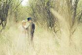 Mladý pár, nově oddaná, oblečený v retro stylu, v zahradě — Stock fotografie
