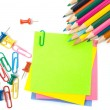 Stock Photo: Colored pencil, clips and note paper on white