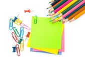 Colored pencil, clips and note paper on white — Stockfoto