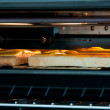 Cheese on toast under grill — Stock Photo #6075729