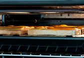 Cheese on toast under grill — Stock Photo