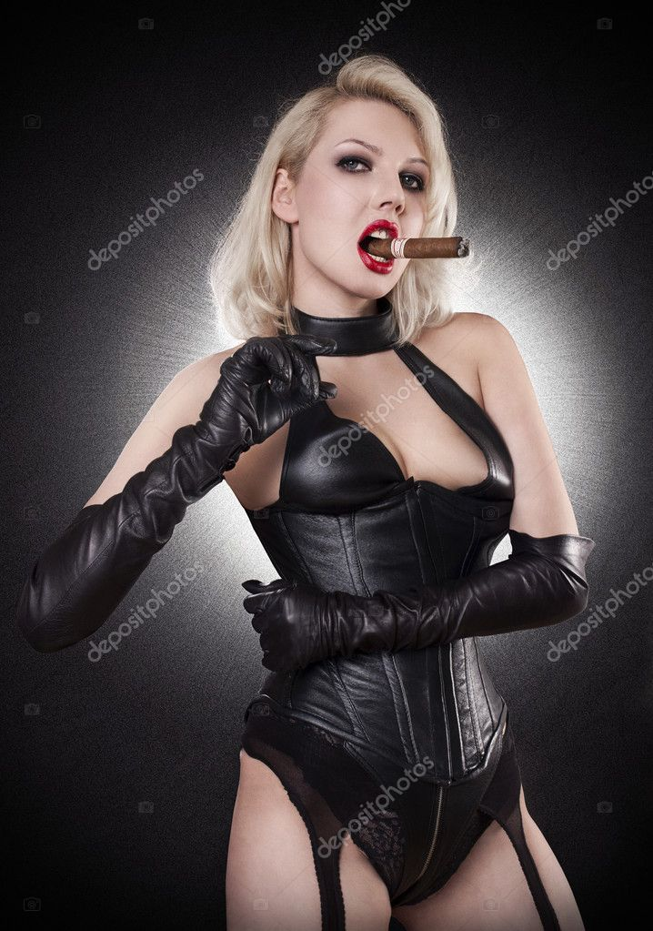 A young blond lady mistress with bright red lips without any emotions smoking cigarette, wearing a black leather corset and gloves on the black background — Stock Photo #6073295