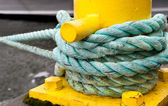 Twisted green rope around a yellow pier — Stock Photo