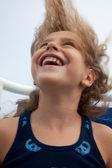 Schattig klein meisje lachen met haar geblazen in de wind. — Stockfoto