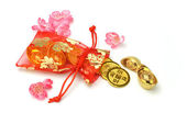 Gold ingots and coins in red sachet — Stock Photo
