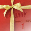 New year calendar page on red gift box — Stock Photo