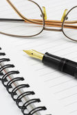 Eyeglasses and fountain pen on notebook — Foto de Stock