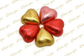Heart shaped chocolates in color wrappings — Stock Photo