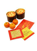 Chinese New Year rice cakes, oranges and red packets — Stock Photo