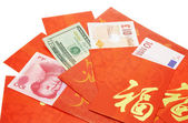 Multi national currency notes in Chinese red packets — Stock Photo