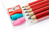 Pencils, sharpener and erasers in plastic box — Stock Photo