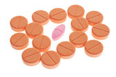 Red pill among orange favored lozenges — Stock Photo