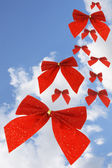 Red bow ribbons in the sky — Stock Photo