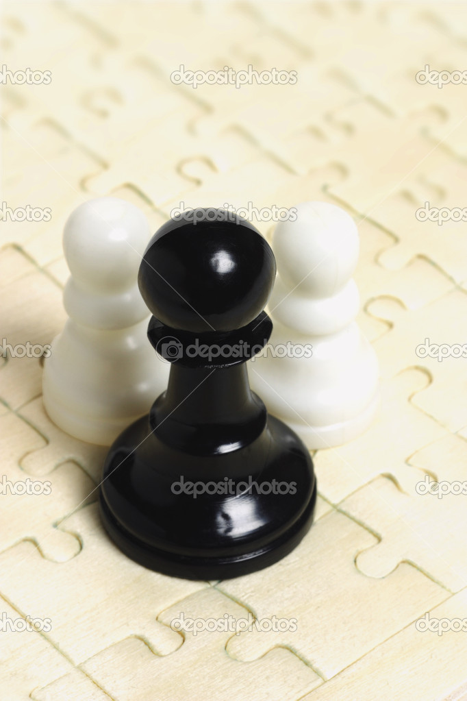 Black and white chess pawns on jig saw puzzle background — Stock Photo #6684818