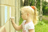 Little girl drawing with chalk on the wall — Stock Photo