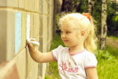 Smiling child drawing with chalk on the wall — Stock Photo