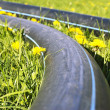 Construction pipes on the grass with dandelions — Stock Photo