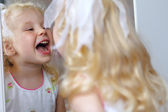 Screaming caucasian girl looking at herself into the mirror — Stock Photo