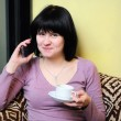 Stock Photo: Girl holding coffee and using her mobile phone
