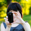 Woman taking photo using her mobile phone — Stockfoto