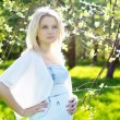 Young pregnant woman in park - Stock Photo