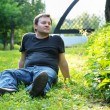 Man sitting on the grass - Stock Photo