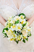 Bride holding beautiful wedding flowers bouquet — Stock Photo