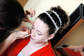 Bride applying wedding make-up by make-up artist — Stock Photo