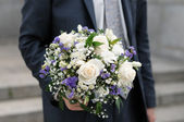 Groom holding wedding bouquet — Stock Photo