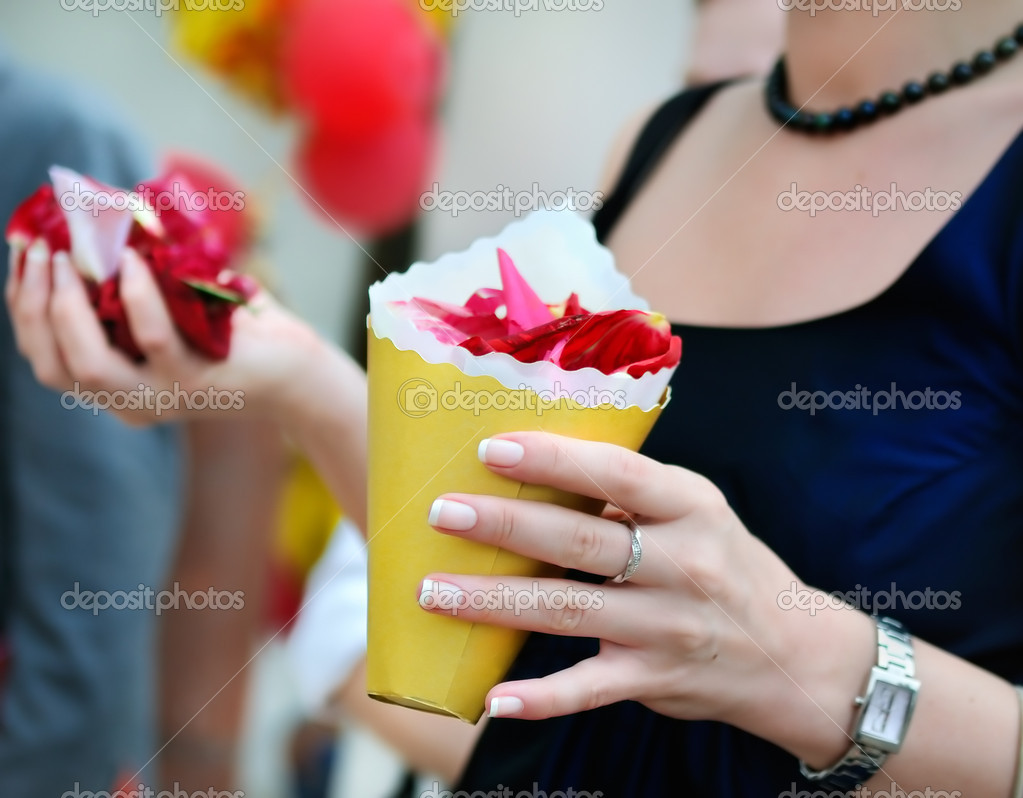 Woman holding yellow paper bag with rose petals  Stock Photo #6074143