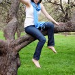Stock Photo: Girl sitting on tree