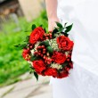 Bride holding red wedding flowers bouquet — Stock Photo #6372681