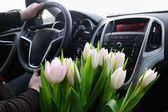 Bunch of tulips in car — Stock Photo