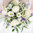 Stock Photo: Bride holding wedding flowers bouquet