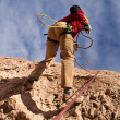Man climbing a mountain in the blue sky — Stock Photo